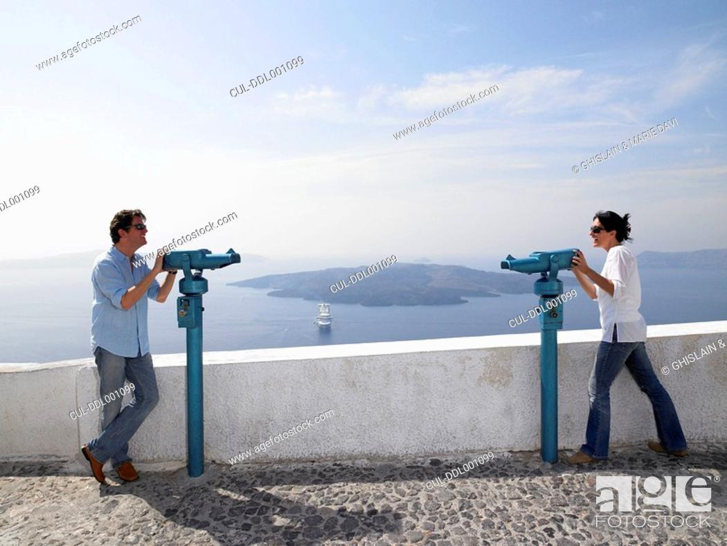 Stock Photo: Couple looking through spyglasses.