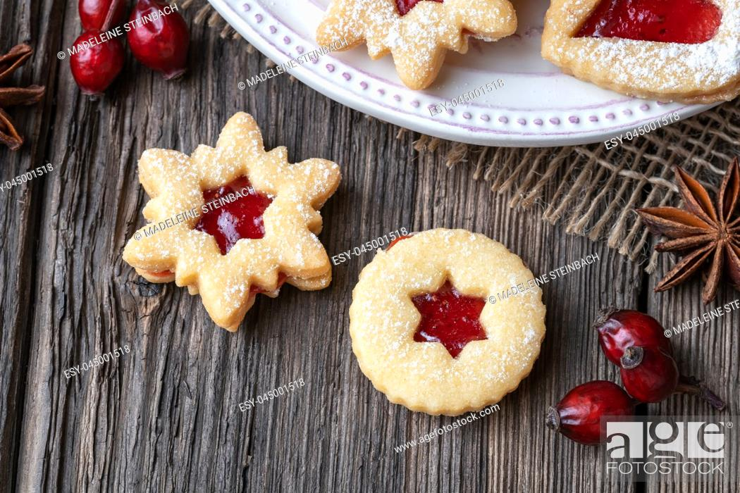 Stock Photo: Traditional Linzer Christmas cookies filled with strawberry jam on a wooden table.