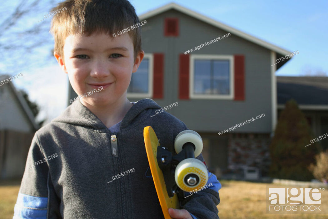 Stock Photo: Boy, age five, looking at camera with skateboard in front of home.