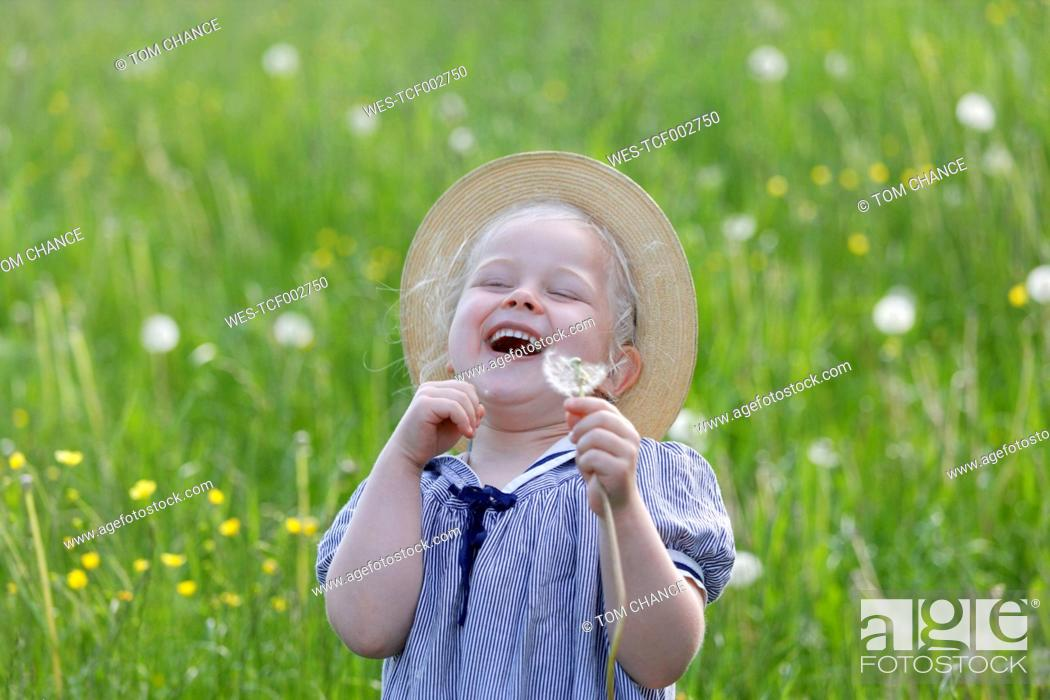 Stock Photo: Germany, Bavaria, Girl with dandelion seed, smiling.