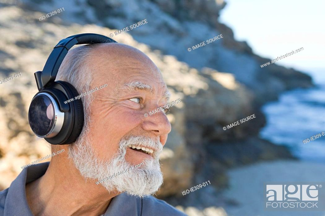 Stock Photo: Senior man listening to music.