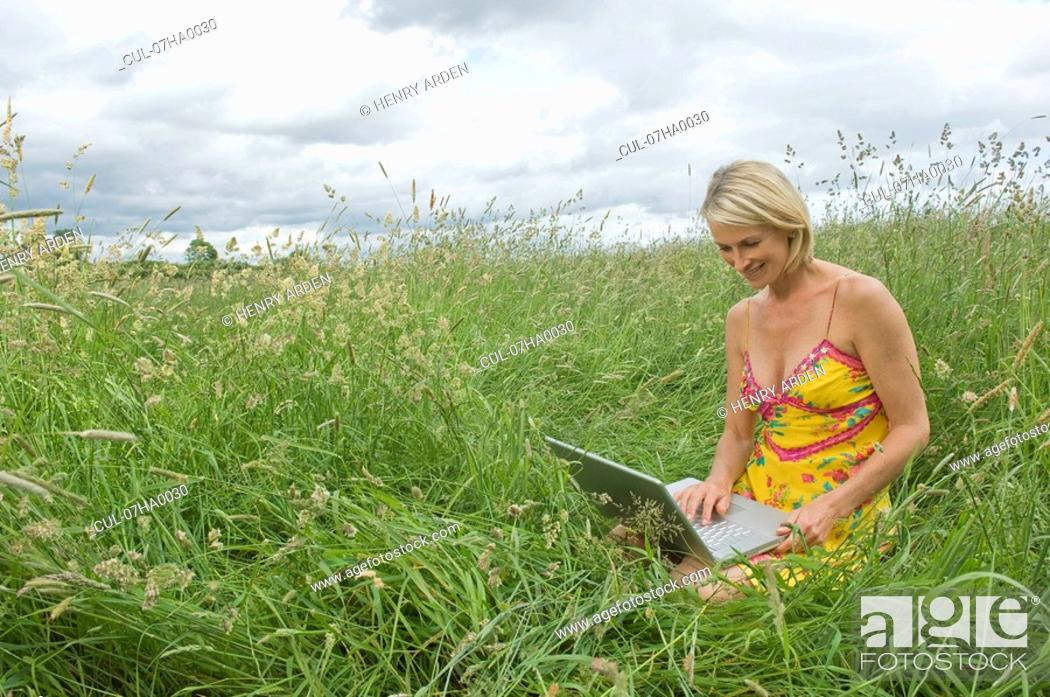 Stock Photo: Woman sitting in field with laptop.