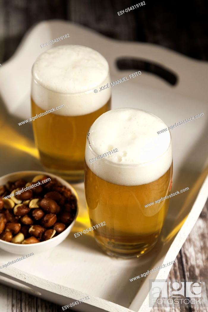 Stock Photo: two glasses of beer with a bowl of peanuts in a tray on wooden table.