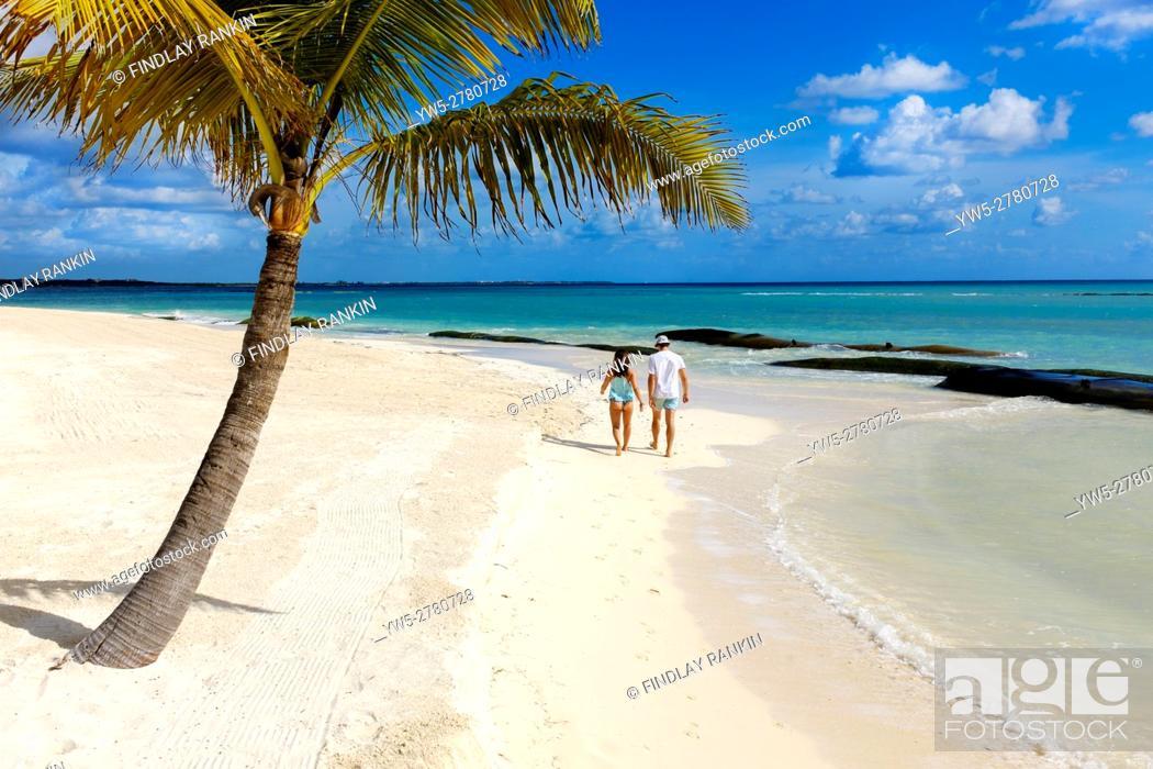 Stock Photo: Young couple walking along the beach at Riviera Maya, Playa del Carmen, near Cancun, Mexico.