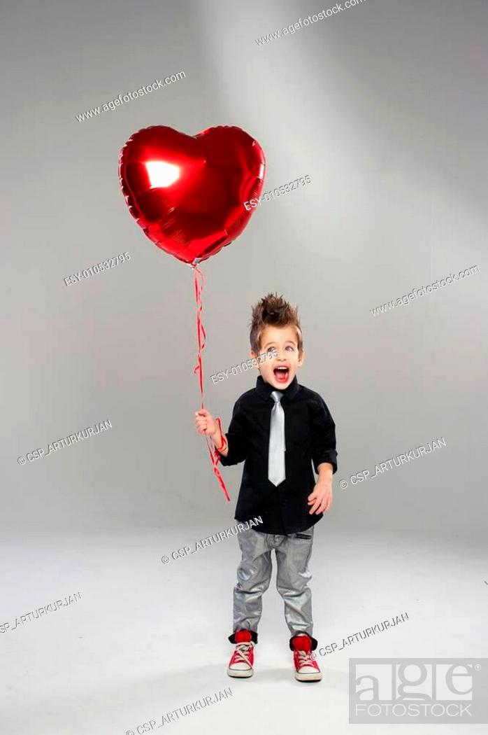 Stock Photo: Happy small boy with red heart balloon on a light background.