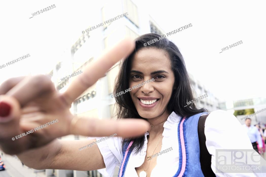 Imagen: Woman doing V sign, wearing Dirndl, brazilian ethnicity. Munich, Germany.