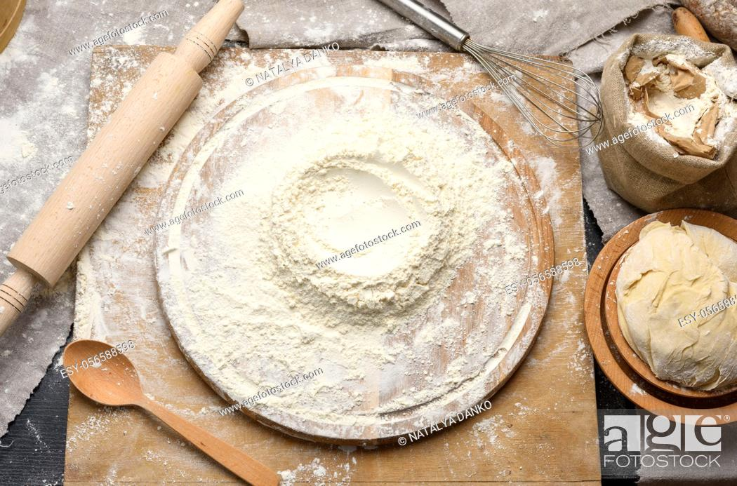 Stock Photo: white wheat flour heaped on a round wooden board, kneaded dough with a wooden plate, top view.