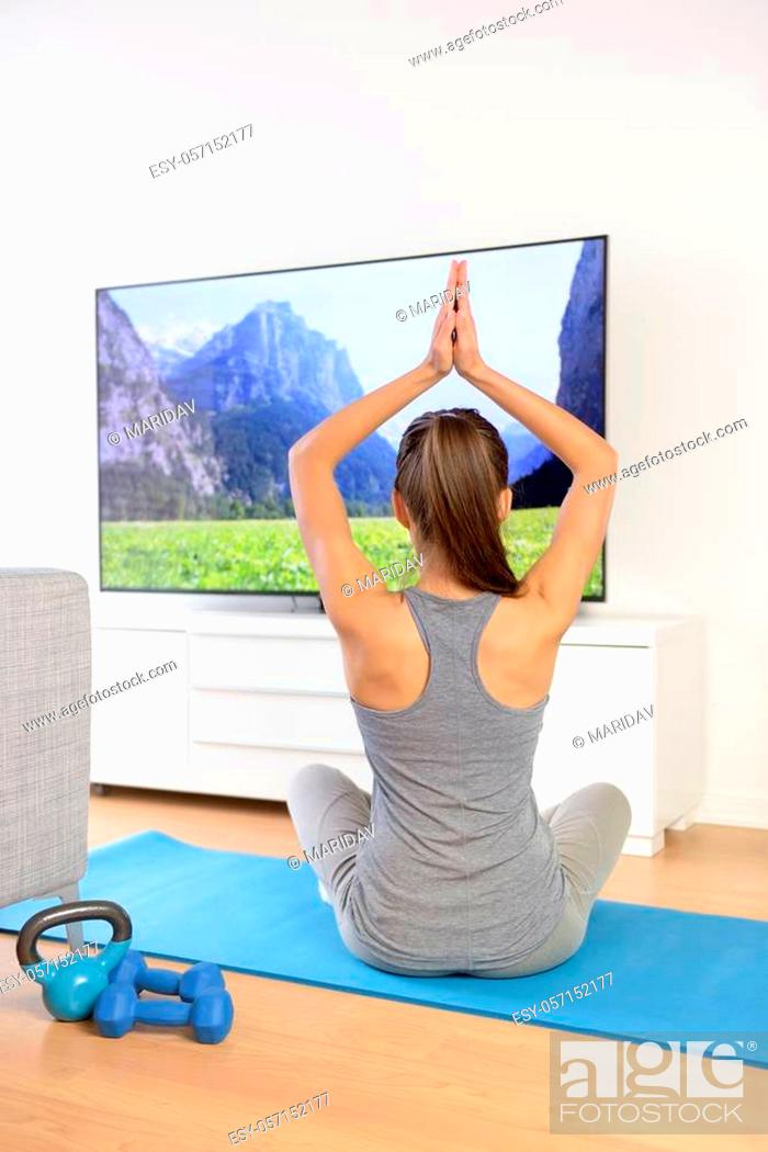 Imagen: Woman doing home yoga meditation in front of TV. Fit girl doing easy pose relaxation exercises watching a TV show or training video with arms raised sitting on.