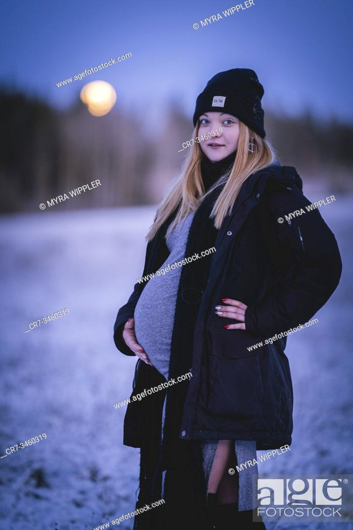 Stock Photo: Portrait of a young pregnant girl soon to become mother, posing in Swedish winter landscape shot with natural light.