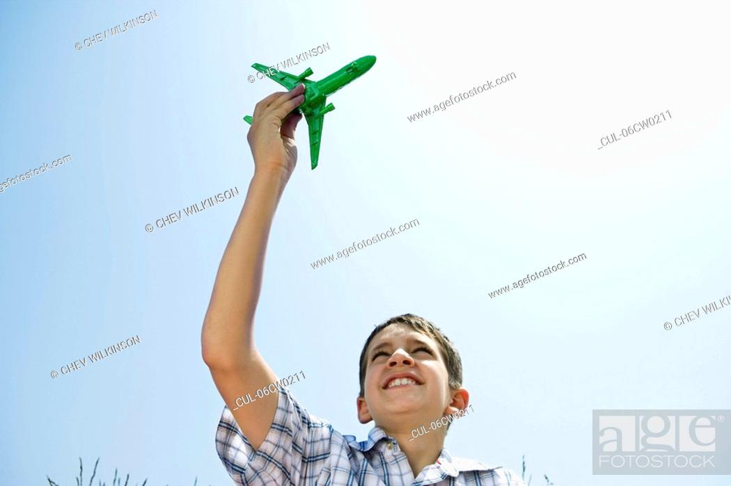 Stock Photo: Boy holding toy plane aloft.