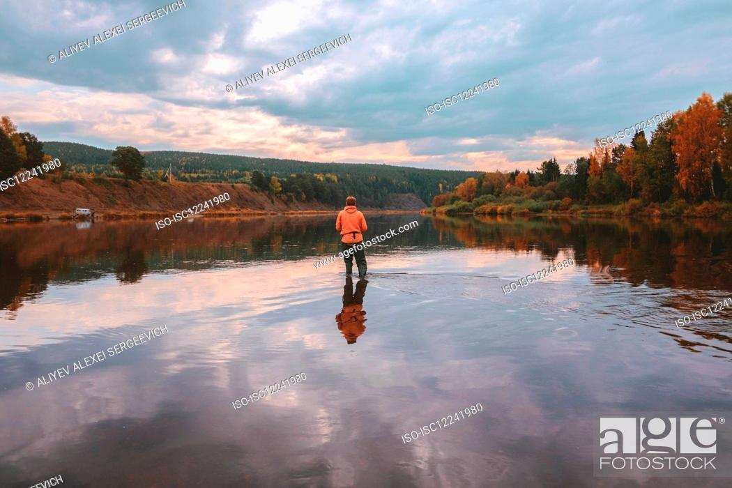 Stock Photo: Angler fishing in middle of lake in autumn, Russia.