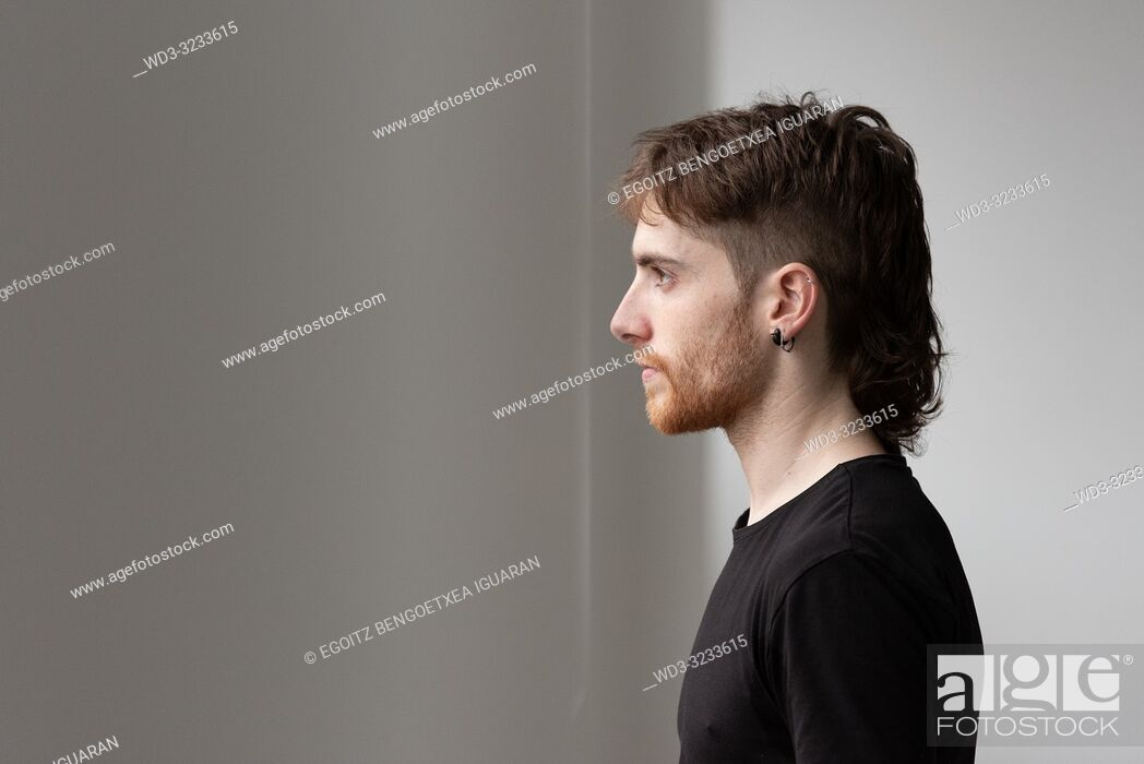 Stock Photo: Portrait of a young adult man looking through the window.