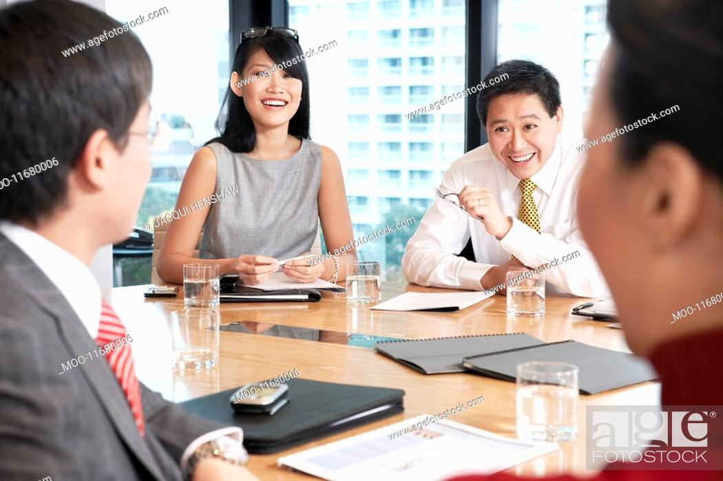 Stock Photo: Business people sitting round table in conference room.
