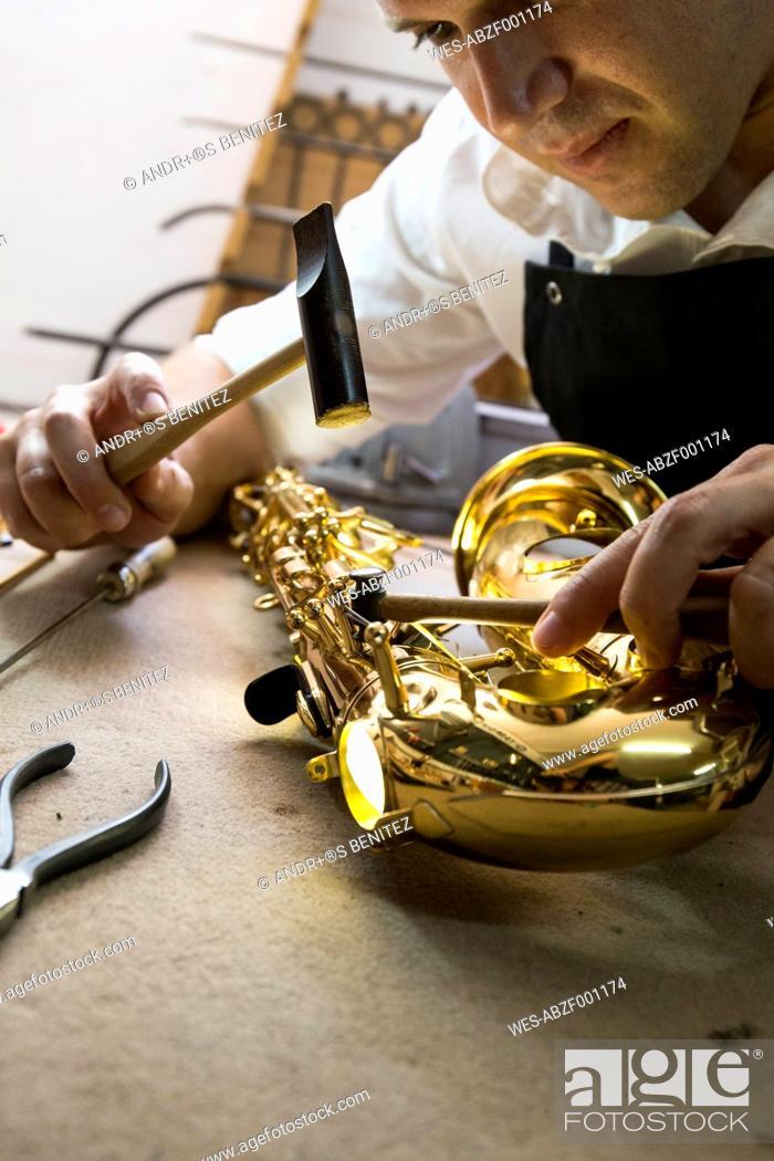 Imagen: Instrument maker using a hammer repairing a saxophone.