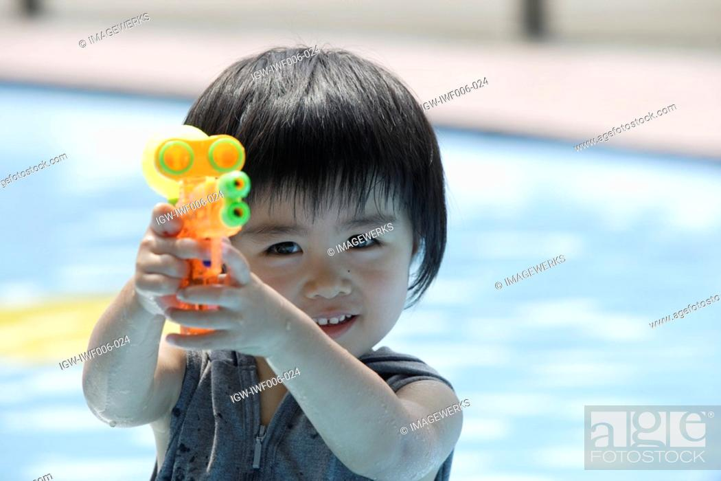 Stock Photo: A boy holding a water pistol.