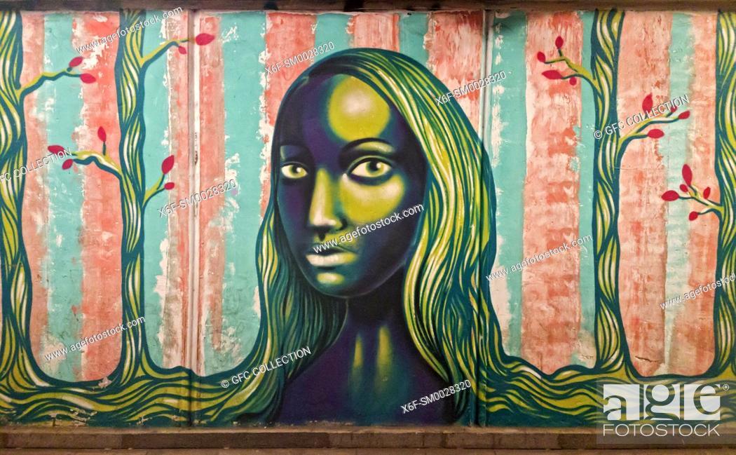Stock Photo: Young woman with long hairs, graffiti, underground passway Baratashvili Bridge, Tbilisi, Georgia.