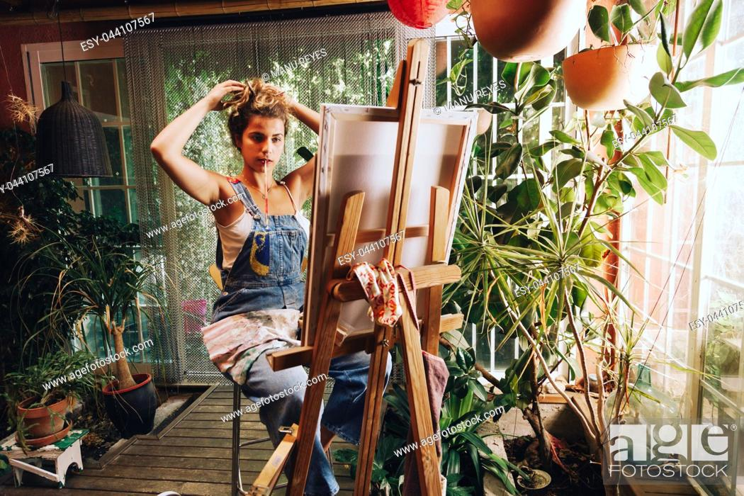 Imagen: Indoor shot of professional female artist painting on canvas in studio with plants.
