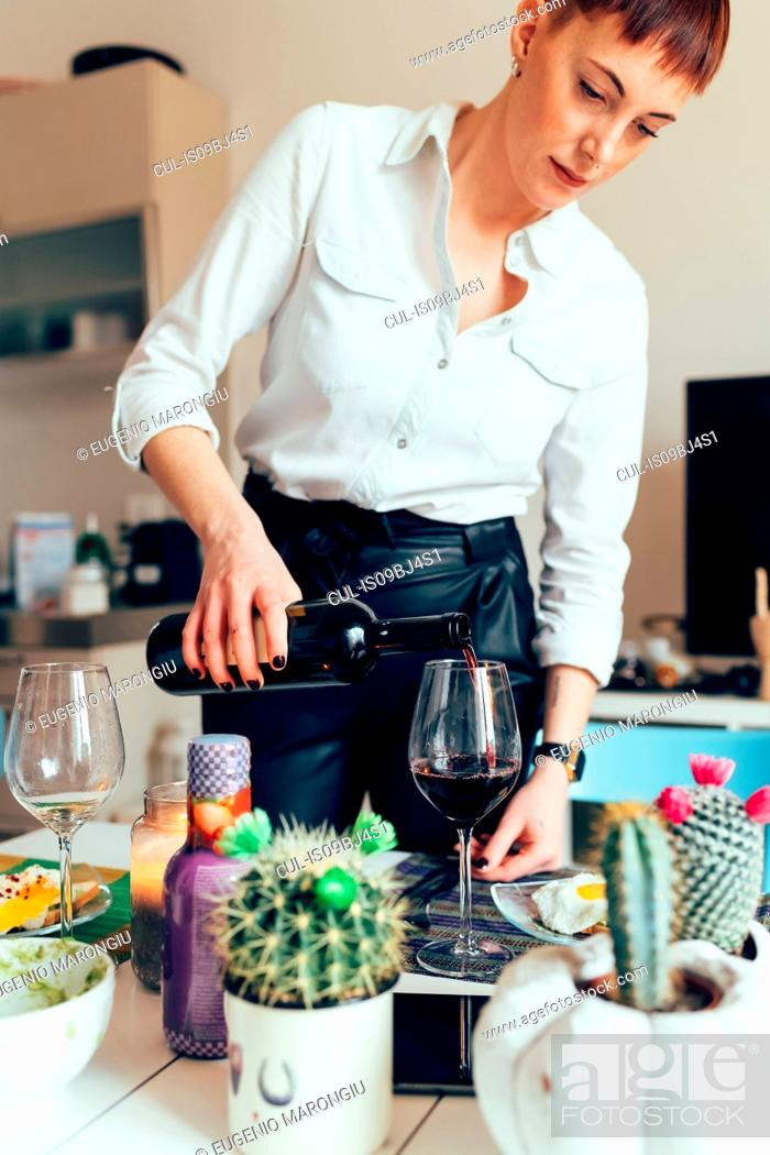 Stock Photo: Woman pouring bottle of wine.