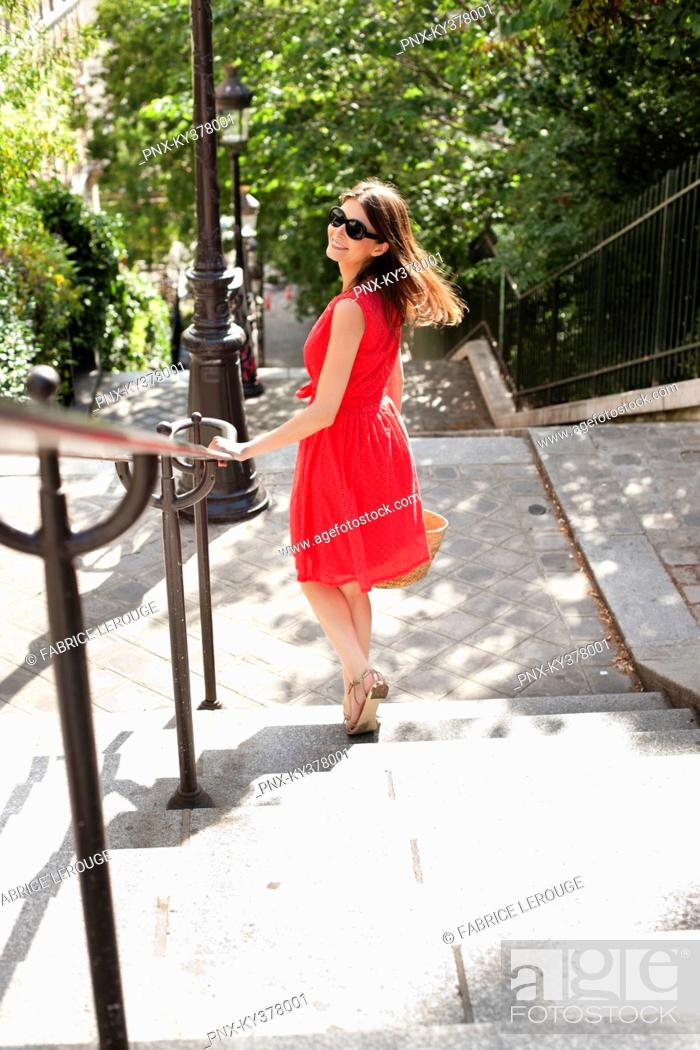 Stock Photo: Woman moving down staircases and smiling, Montmartre, Paris, Ile-de-France, France.