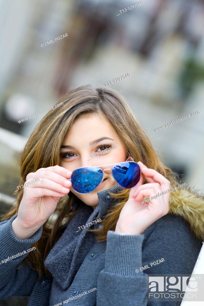 Stock Photo: Teenage girl portrait happy with sunglasses in hand.