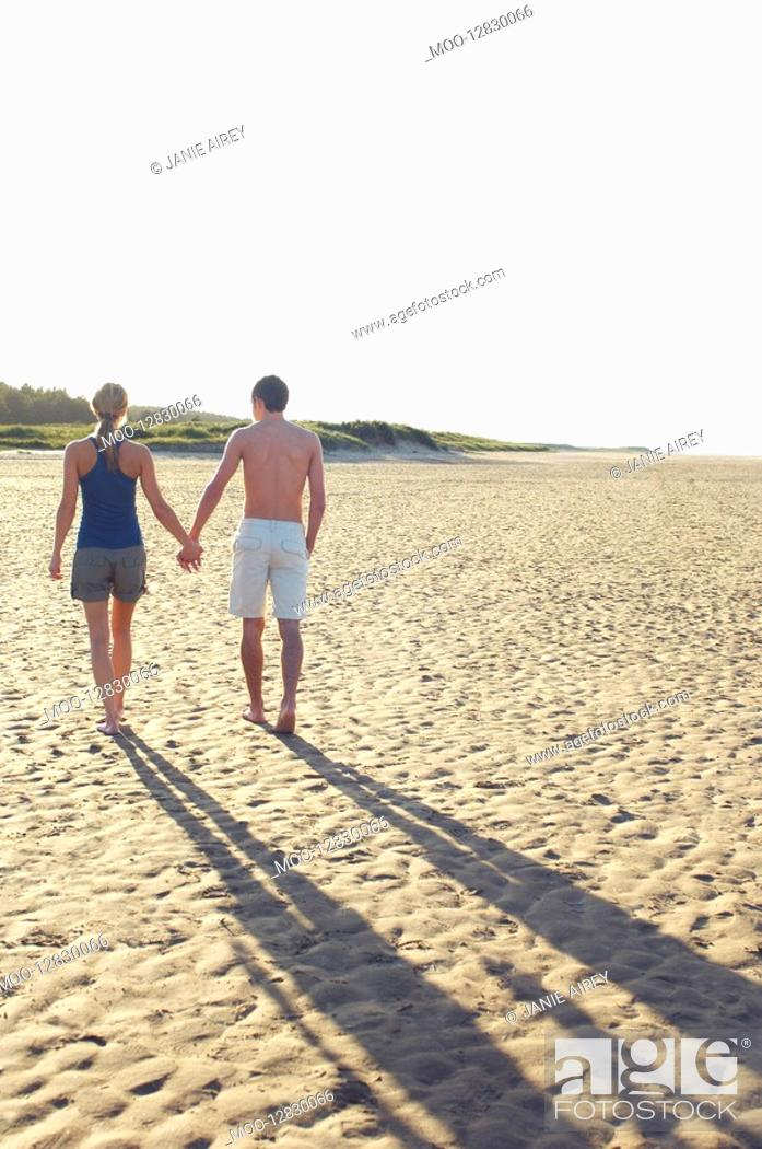 Stock Photo: Couple Walking on Beach holding hands back view.