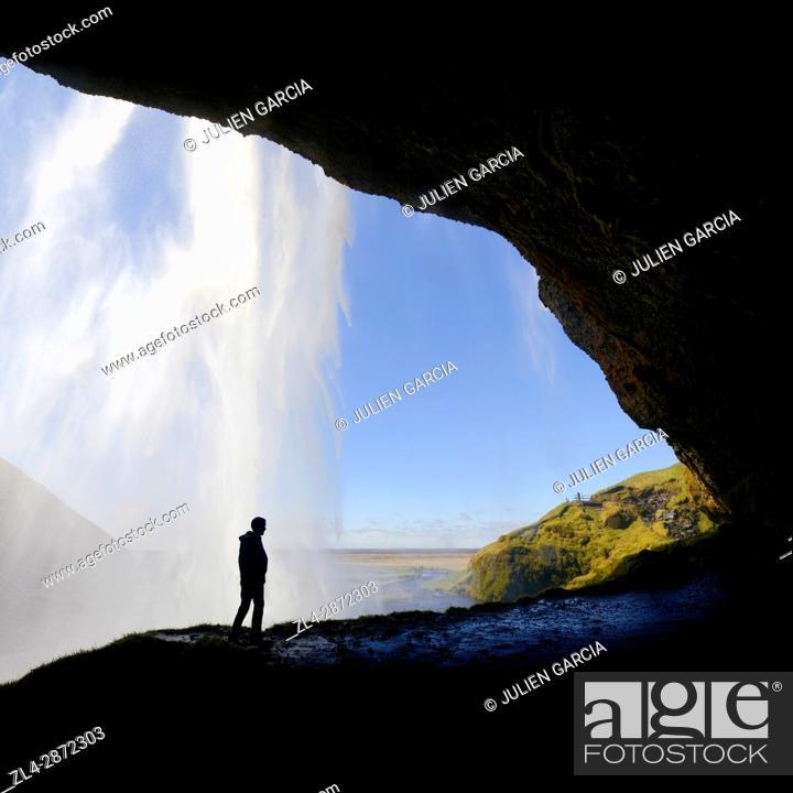 Stock Photo: Iceland, Sudurland region, Seljalandsfoss waterfall, silhouette of man on a path passing behind the waterfall.