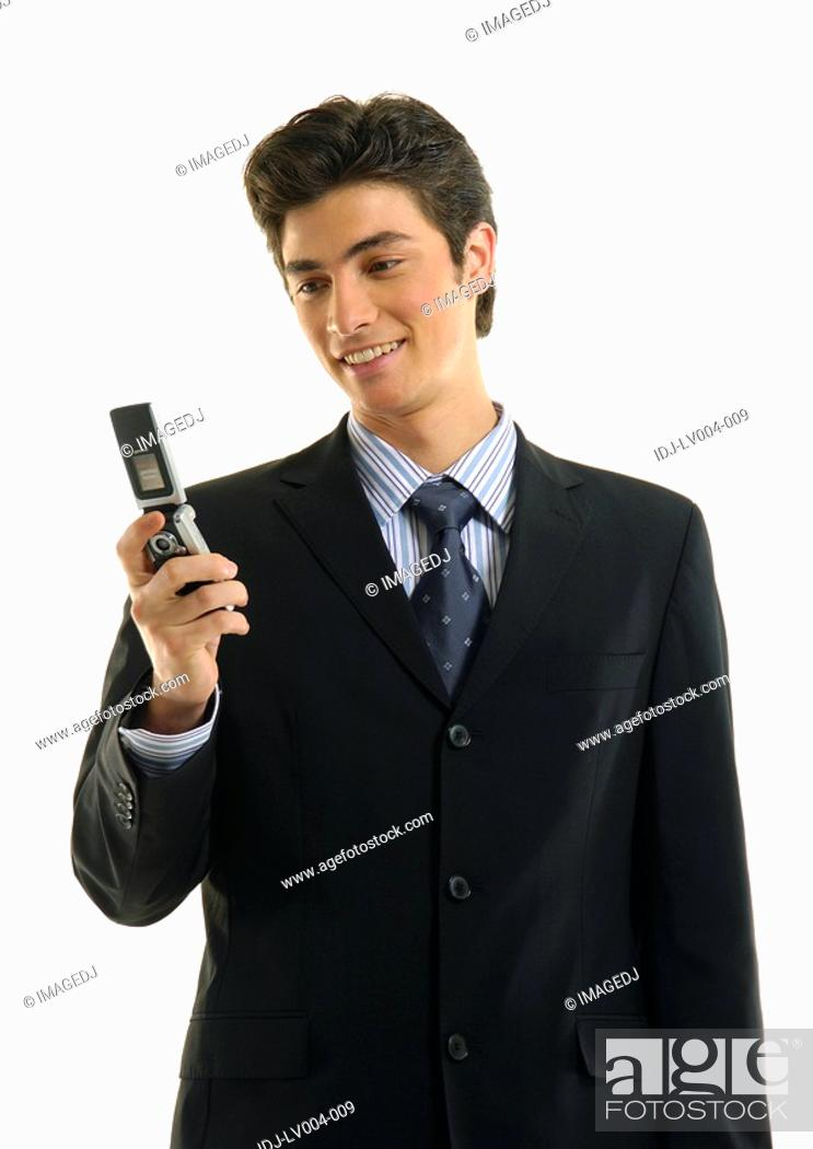 Stock Photo: Businessman text messaging with a mobile phone and smiling.