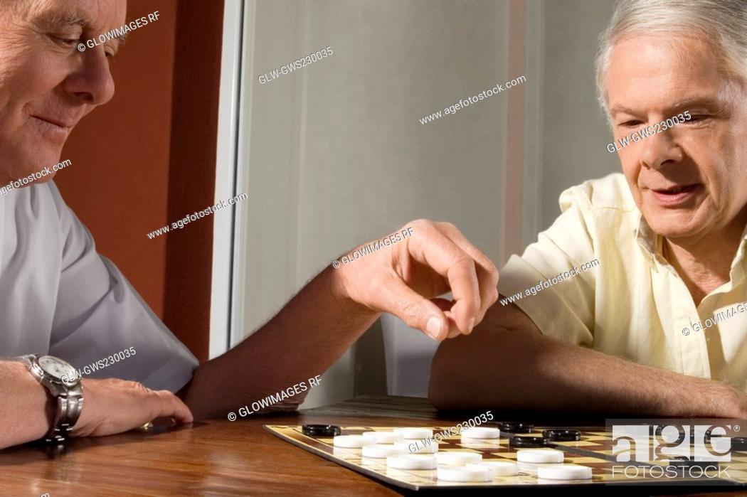 Stock Photo: Two senior men playing checkers.