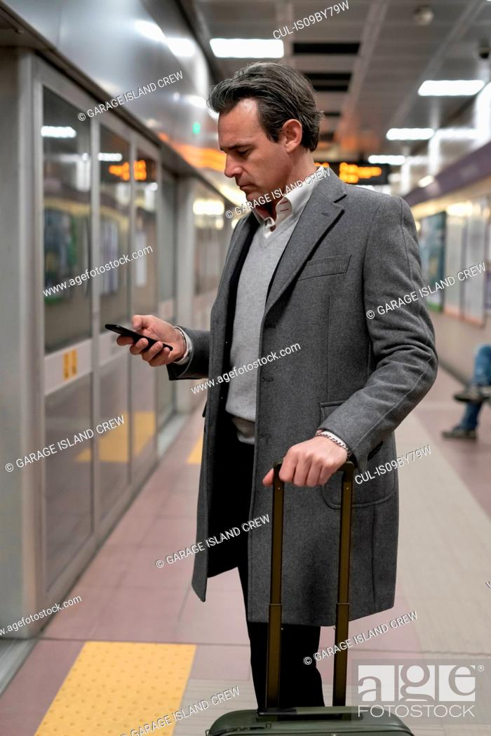 Stock Photo: Businessman using smartphone on train platform.