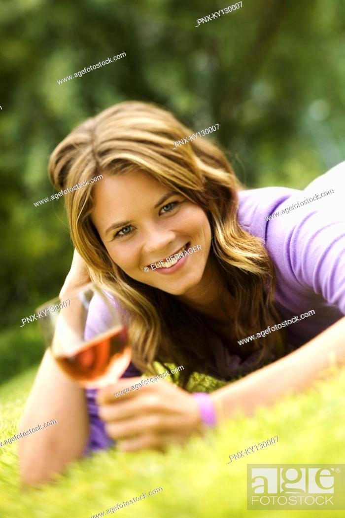 Stock Photo: Young smiling woman lying on grass, glass of wine.