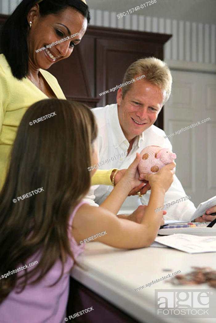 Stock Photo: Side profile of a daughter showing a piggy bank to her parents.
