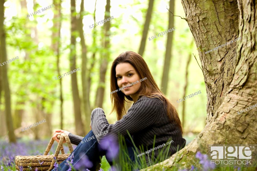 Stock Photo: A young woman sitting under a tree, holding a picnic basket.