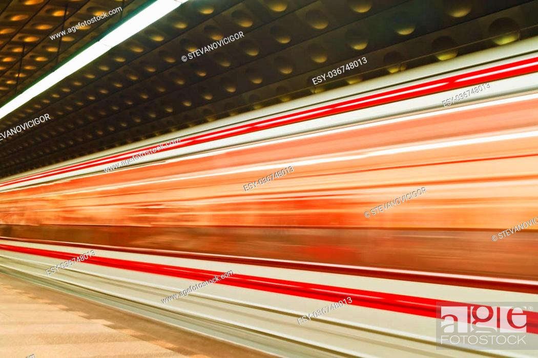 Stock Photo: Fast blurred trail of train in traffic motion in illuminated public metro station.