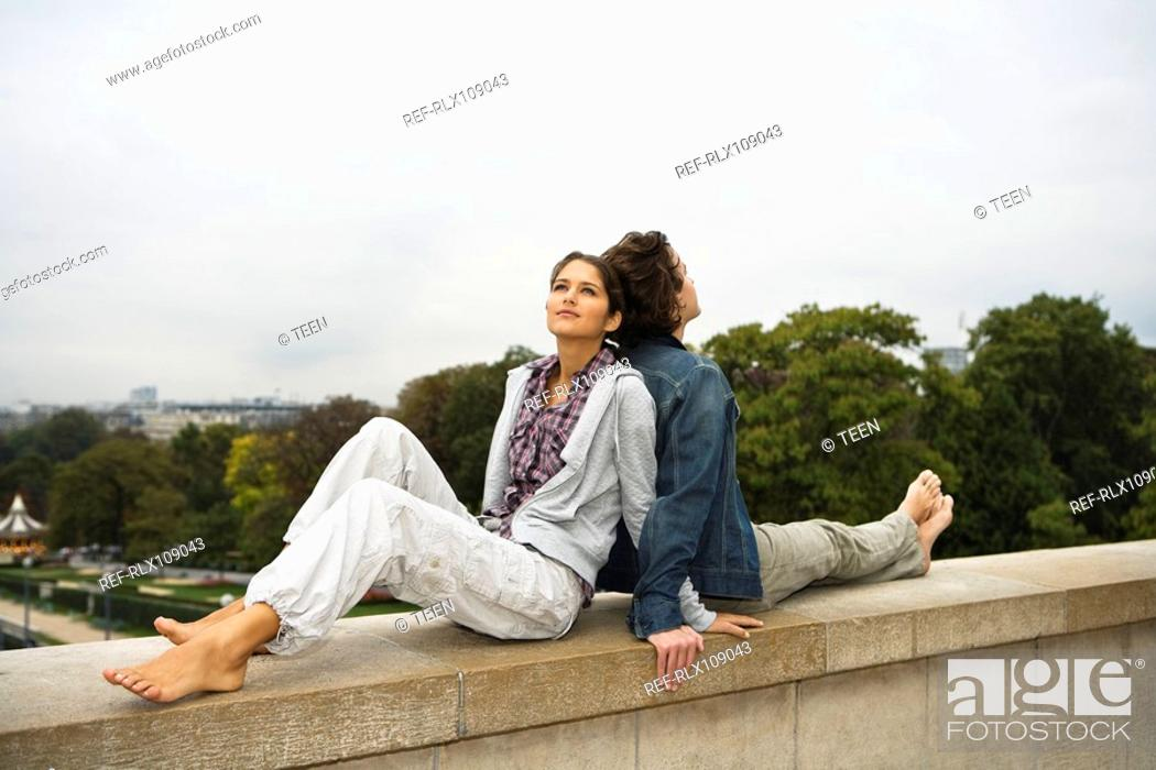 Stock Photo: Young couple lying back to back on wall, Paris France.