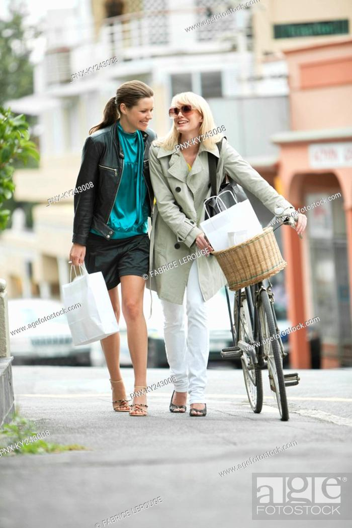 Stock Photo: Two women walking with shopping bags.