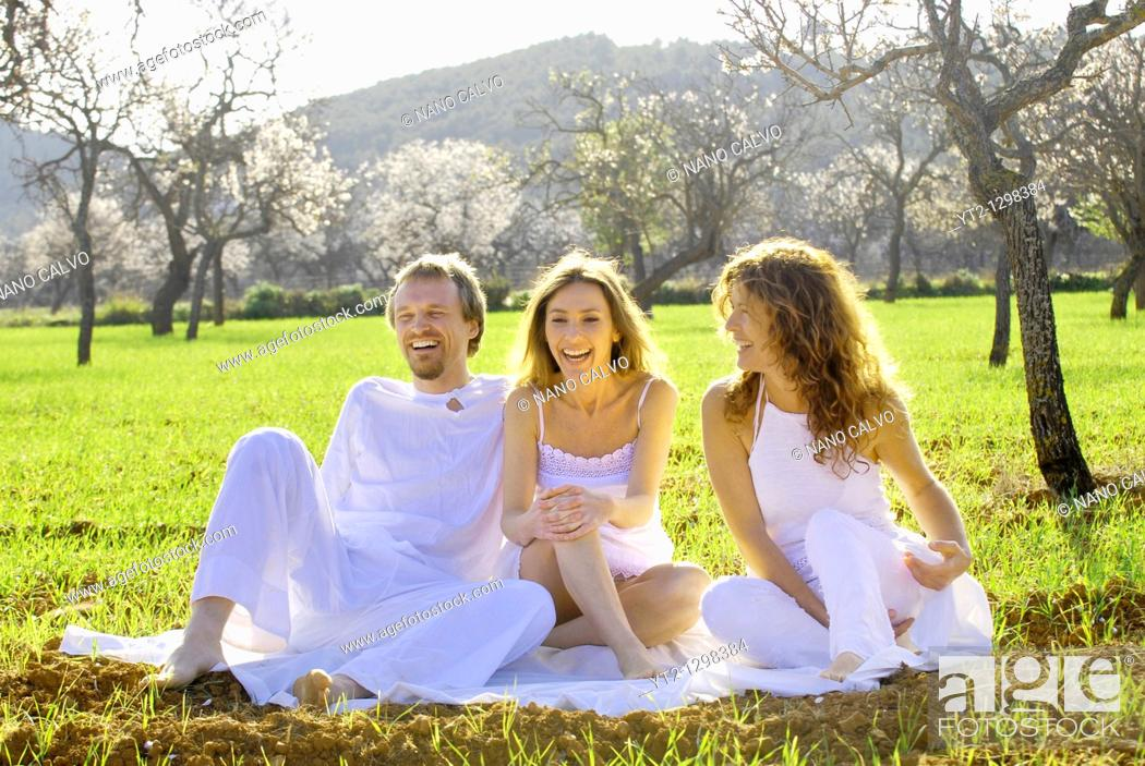 Stock Photo: Three friends, a spanish woman, a brazilian woman and a sweedish man, enjoying themselves in the fields of Ibiza, Spain.