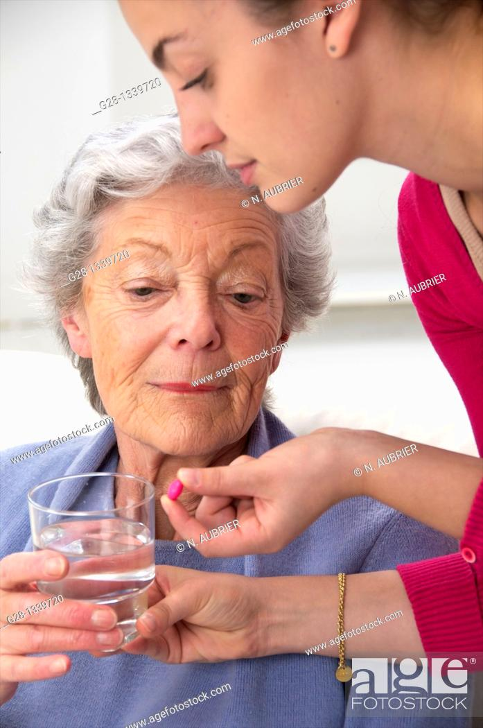Stock Photo: Senior woman in a mauve cardigan, holding a glass of water, and young help giving her a red tablet at home.