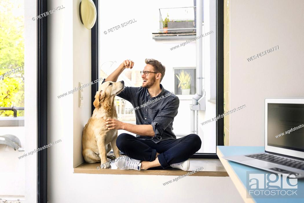 Stock Photo: Happy man with dog sitting at the window.