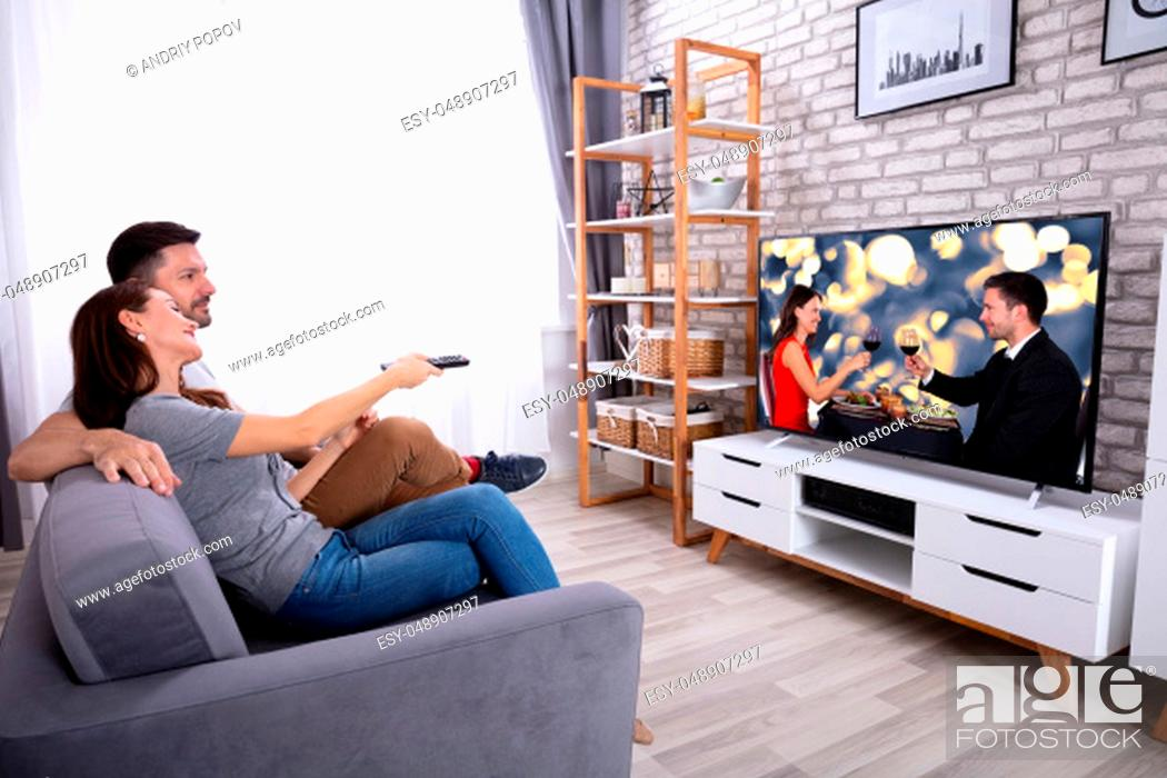 Stock Photo: Young Couple Sitting On Sofa Watching Television At Home.