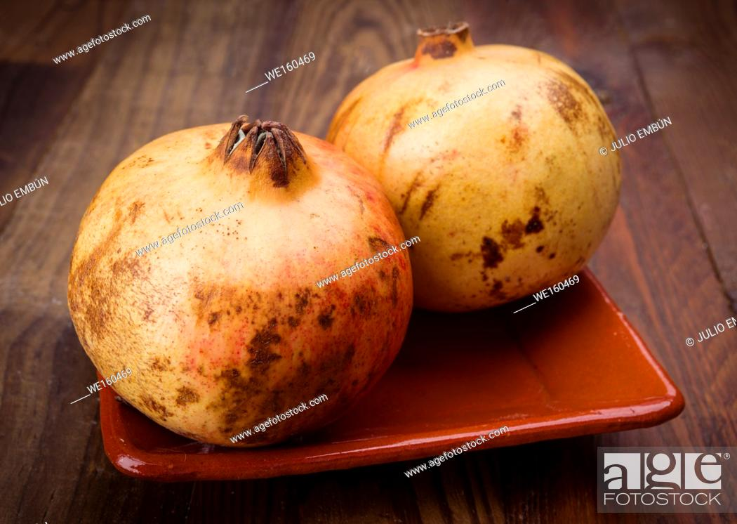 Stock Photo: whole pomegranates in rustic wood.