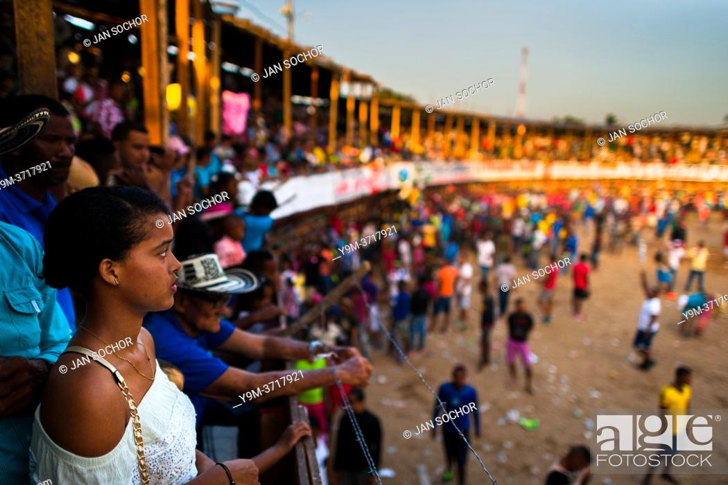 Stock Photo: A young Colombian woman looks down at the amateur bullfighters in the arena of Corralejas, a rural bullfighting festival held in Soplaviento, Colombia.