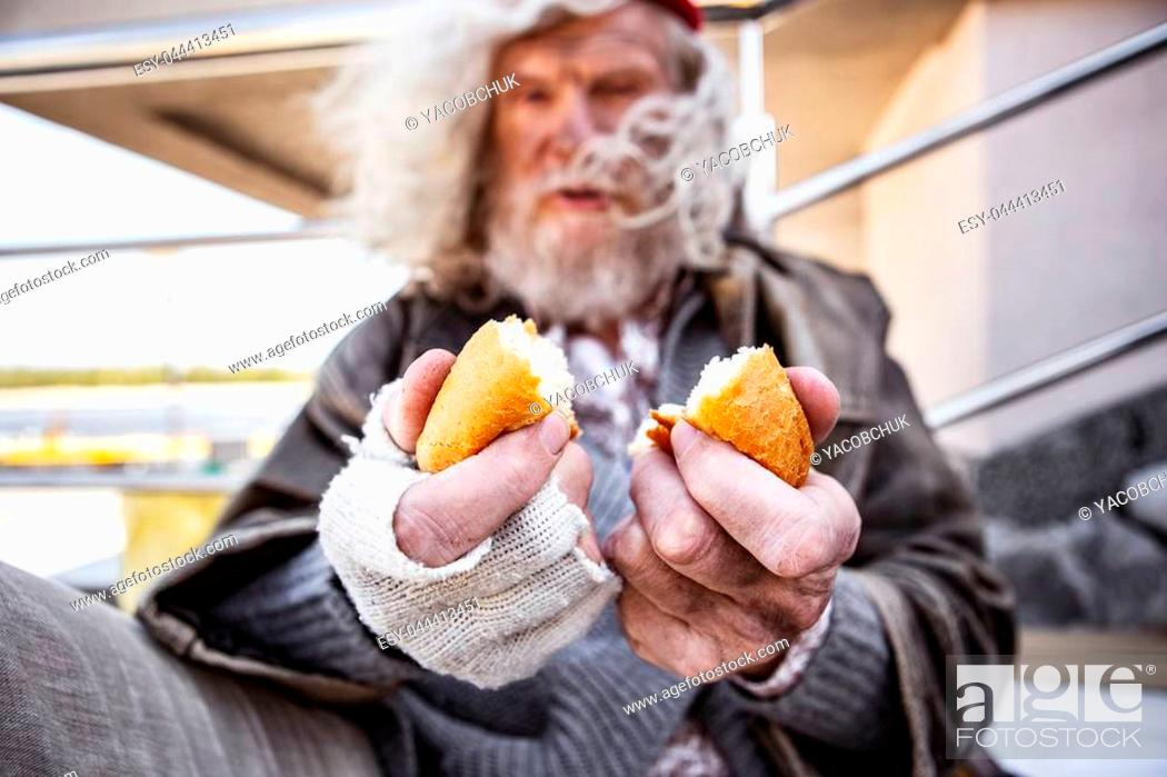 Stock Photo: Piece of bread. Selective focus of delicious food being in hands of an aged homeless man.