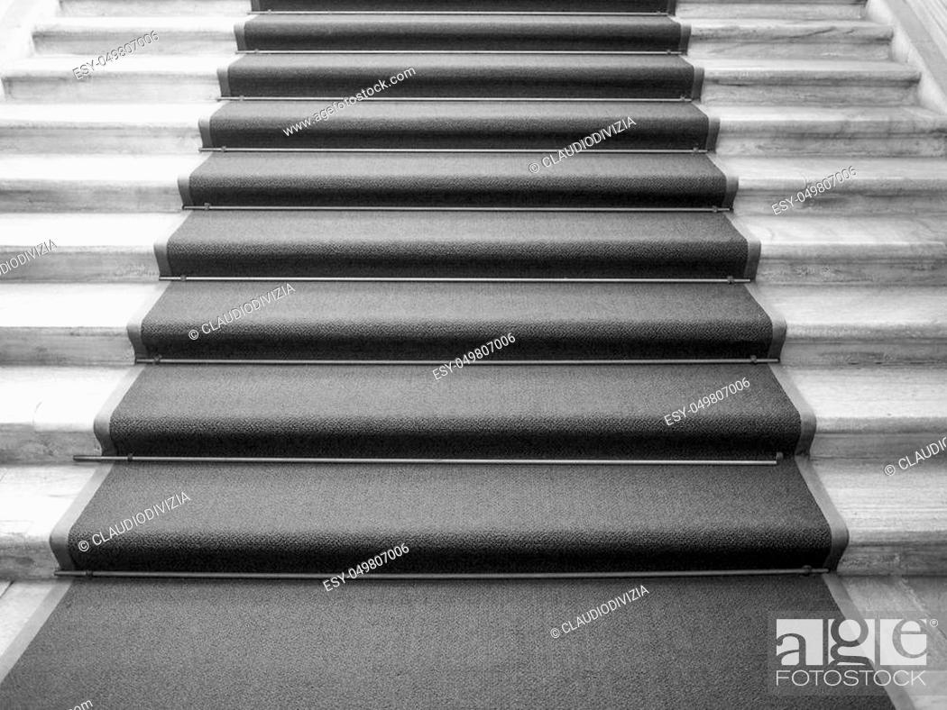 Stock Photo: Red carpet on a stairway used to mark the route taken by heads of state, vips and celebrities on ceremonial and formal occasions or events in black and white.