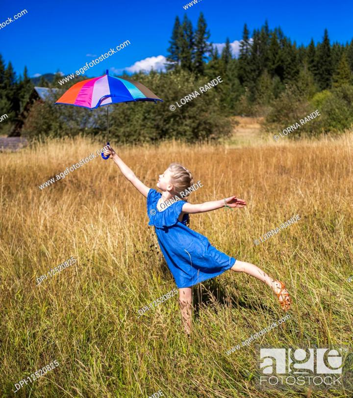 Stock Photo: A young girl stands in a grass field holding an umbrella high and balancing on one foot; Salmon Arm, British Columbia, Canada.