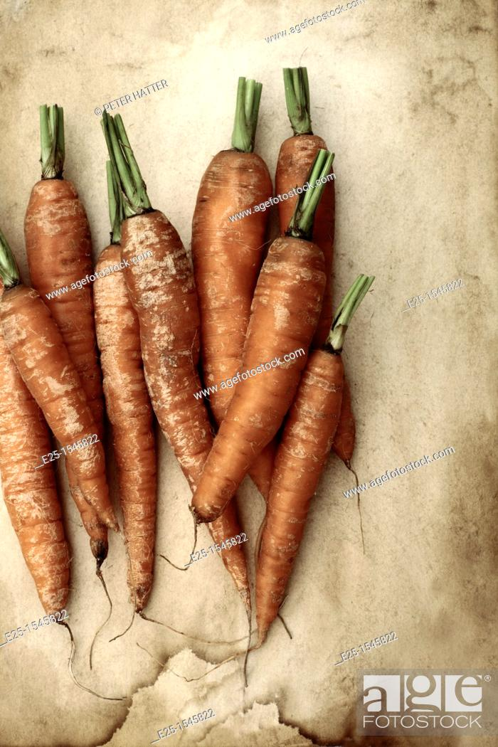 Stock Photo: Carrots organically grown on a textured background.