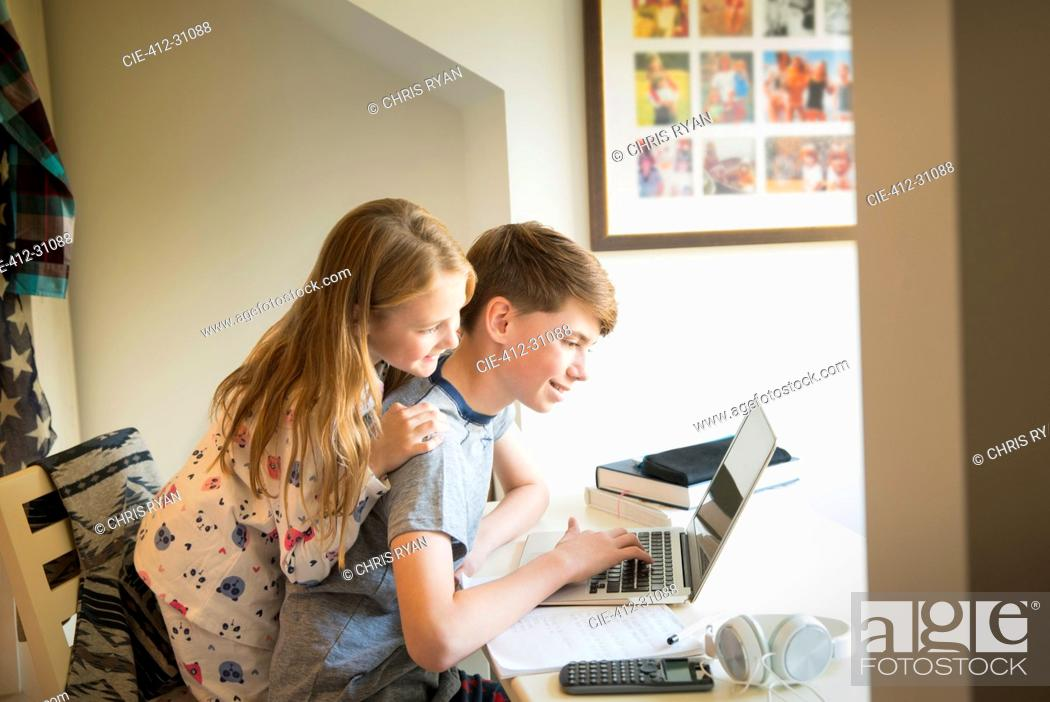 Stock Photo: Sister watching brother using laptop in bedroom.
