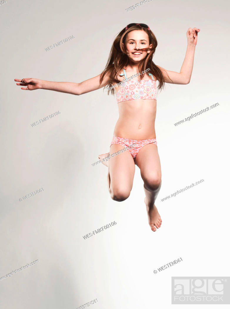Stock Photo: Girl 10-11 jumping and smiling, portrait.