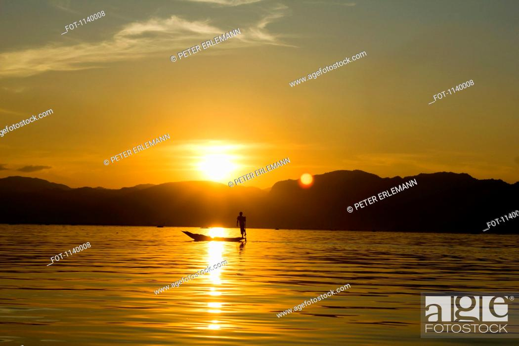 Stock Photo: A silhouette of a person fishing, Inle Lake, Burma.