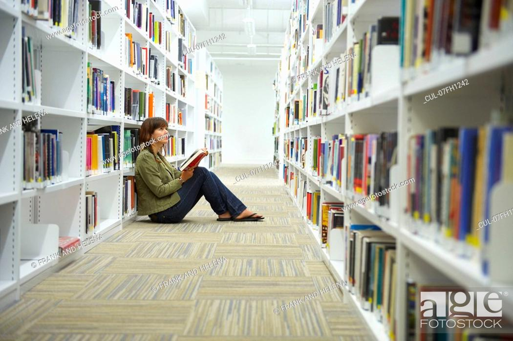 Stock Photo: Young woman sitting on library floor.