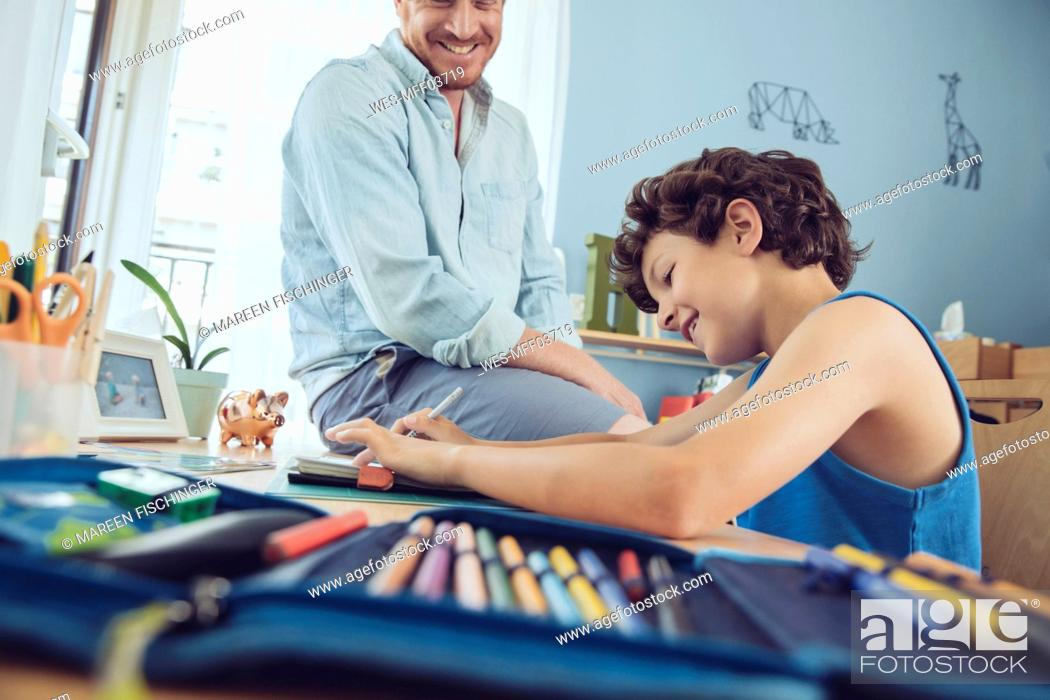 Stock Photo: Father helping boy doing his schoolwork at home.